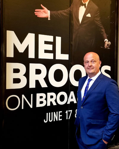 Todd Peterson standing next to a Mel Brook poster at a Mel Brooks related event